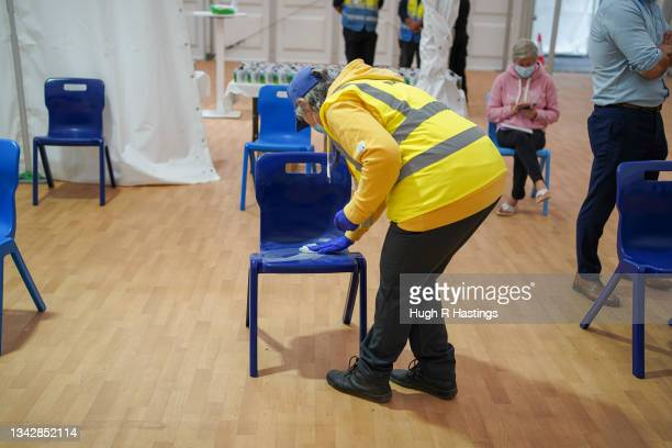 An NHS volunteer cleans a chair at the Stithians Showground temporary NHS vaccination centre during its final hour of opening on September 26, 2021...