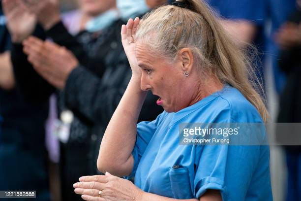 An NHS worker becomes emotional after taking part in a minutes silence outside Salford Royal Hospital on April 28, 2020 in Salford, United Kingdom....