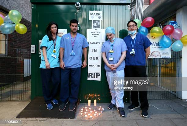 An NHS workers stand for a photo after they lay down candles in memory of a colleague at Newham University Hospital on April 23 2020 in London United...