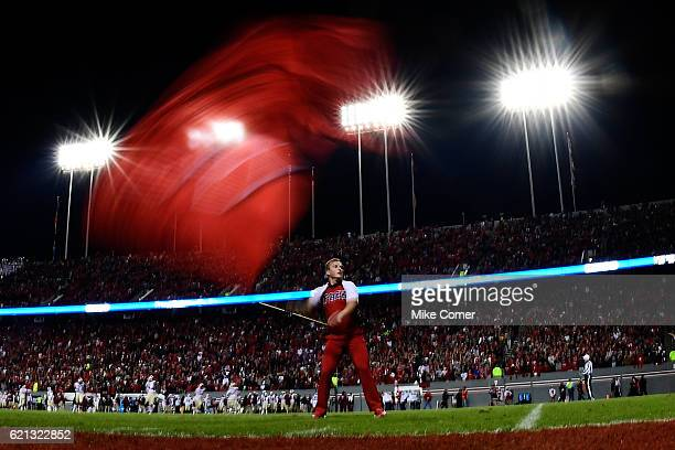 An North Carolina State Wolfpack cheerleader waves an NC State flag following a score against the Florida State Seminoles at CarterFinley Stadium on...