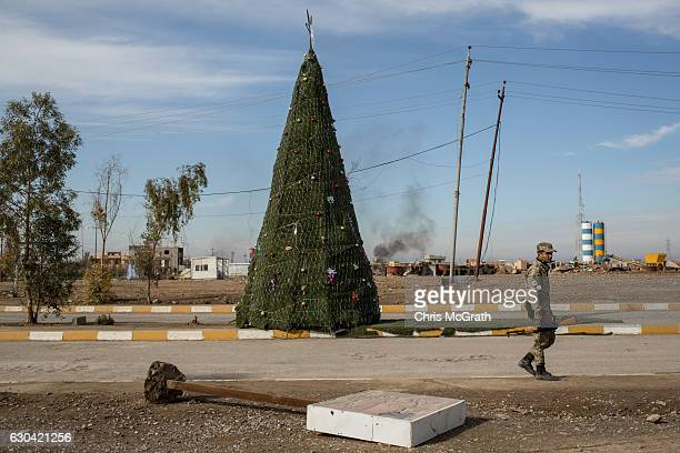 An NPU fighter walks in front of a large Christmas tree erected on the main road on December 22 2016 in Mosul Iraq After recently being liberated...