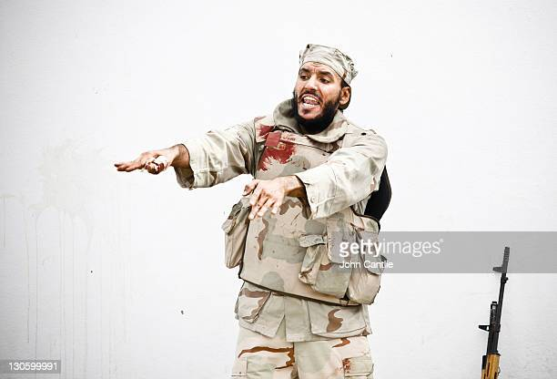 An NTC fighter shouts a warning to comrades after being wounded during fighting in Colonel Gaddafi's home city of Sirte on Oct6ober 12 2011 in Libya...