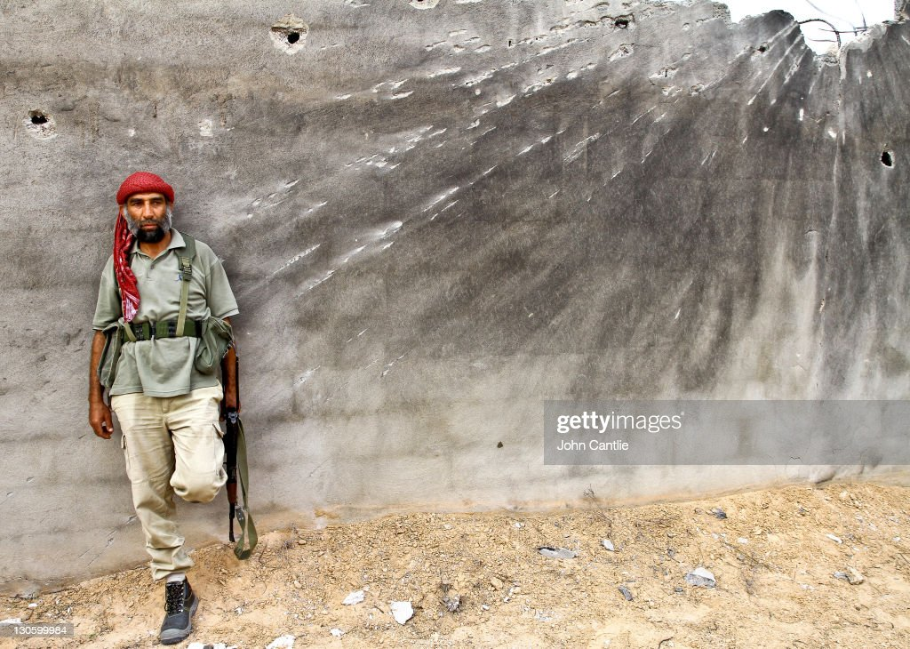 An NTC fighter takes cover behind a concrete wall damaged by rocket blasts in the Dollar Complex of Colonel Gaddafi's home city of Sirte on October 14, 2011 in Libya. NTC forces are continuing their advance on Colonel Muammar Gaddafi's hometown of Sirte.
