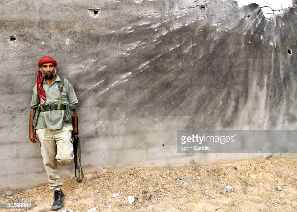 An NTC fighter takes cover behind a concrete wall damaged by rocket blasts in the Dollar Complex of Colonel Gaddafi's home city of Sirte on October...