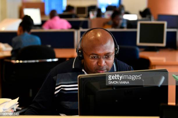 An NTV news reporter works at his desk in a newsroom of Kenyan 'Nation Media Group' in Nairobi on January 19 2018 / AFP PHOTO / SIMON MAINA