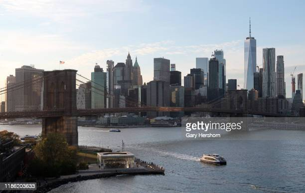 An NYC East River ferry sails in front of the Brooklyn Bridge Jane's Carousel and lower Manhattan on November 4 2019 in New York City
