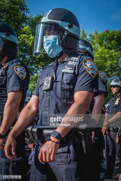 An NYPD officer in riot gear seen with his badge number and face covered at the protest, this practice is widely used to make difficult to report...