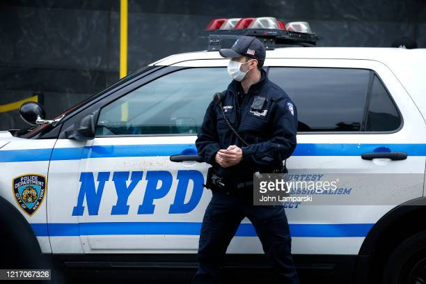 An NYPD officer stands near his patrol car amid the coronavirus pandemic on April 5, 2020 in New York City. COVID-19 has spread to most countries...
