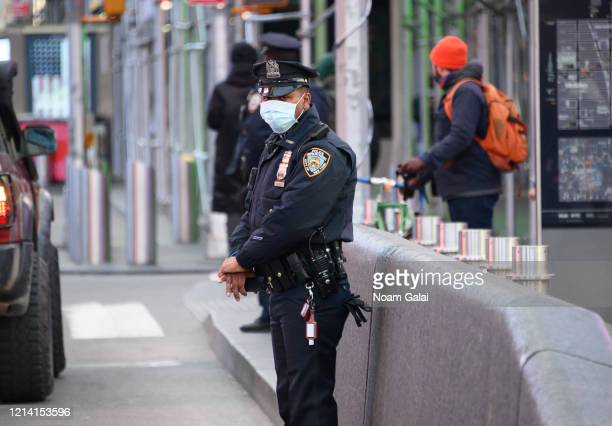 An NYPD police officer wearing a protective face mask is seen in Times Square hours ahead of the implementation of 'New York State on PAUSE'...