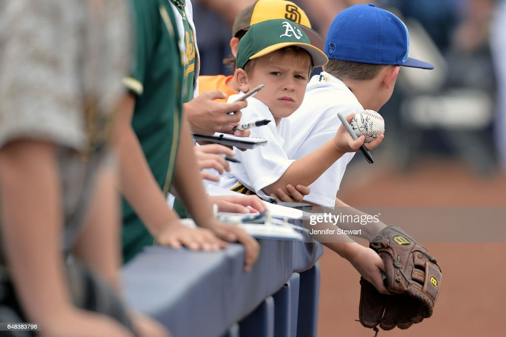An Oakland Athletics fan holds up his autographed ball prior to the spring training game against the Seattle Mariners at Peoria Stadium on March 5, 2017 in Peoria, Arizona.