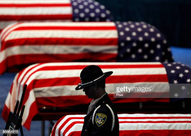An Oakland Police honor guard stands his post next to the flagdraped caskets of Oakland Police Officers Sgt Mark Dunakin John Hege Sgt Ervin Romans...