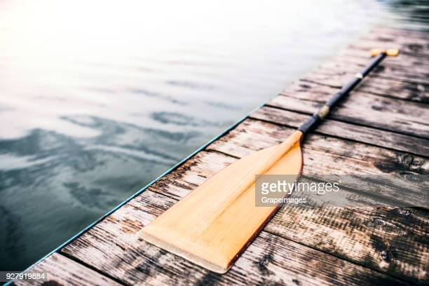 an oar on a wooden decking, water in the background. - paddle stock pictures, royalty-free photos & images