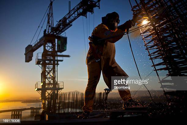 An OAS SA welder cuts a piece of steel during the construction of a bridge over Guanabara bay at the site of the Transcarioca in Ilha do Fundao metro...