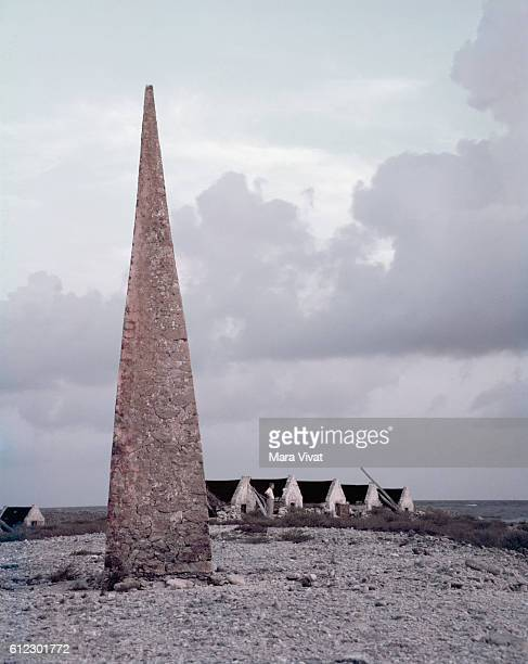 An obelisk stands on a beach beside a row of slave quarters The obelisk directed ships to the settlement on Bonnaire Netherlands West Indies