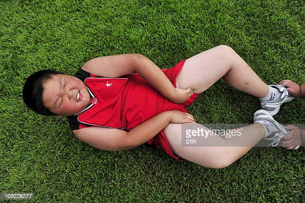 An obese Chinese boy does situps as he takes part in a weightlost camp in Shenyang northeast China's Liaoning province on August 3 2010 A third of...