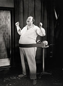 An obese man sings as a motorized belt vibrates on his stomach picture id517322662?s=170x170
