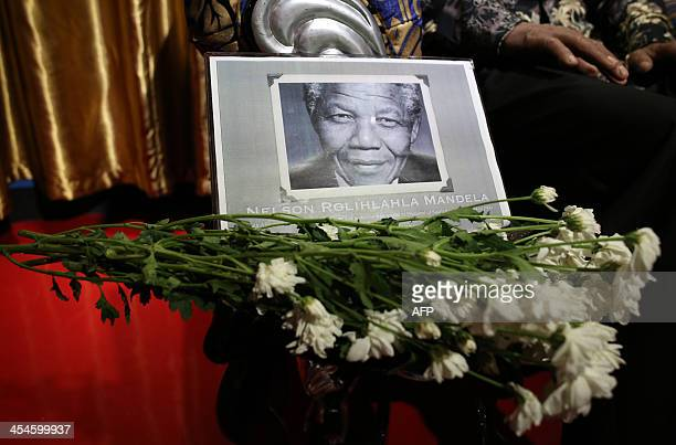 An obituary is displayed next to a wax figure of late former South African president Nelson Mandela at the iCity Red Carpet Wax Museum in Shah Alam...