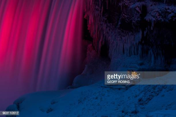 TOPSHOT An observation point at the base of Niagara Falls in Niagara Falls Ontario is covered in ice as the falls are illuminated by colored light on...