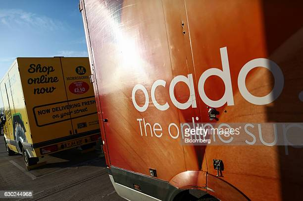 An Ocado branded customer delivery vehicle stands next to Wm Morrisons Supermarkets Plc delivery vehicle outside the Ocado Group Plc distribution...
