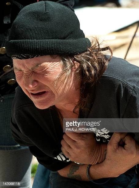An Occupy DC protester cries in pain as US Park Police confiscate tents tarps furniture and other items to remove them from the area using a pickup...
