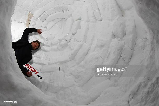 An occupy protester poses with a placard reading 'Occupy WEF' inside an igloo built at the protesters' encampment on January 25 2012 in Davos...
