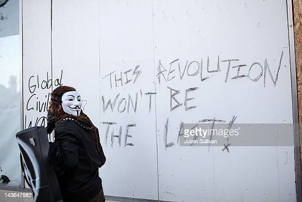 An Occupy protester wearing a Guy Fawkes mask walks by a message written on a wall during a May Day demonstration on May 1 2012 in Oakland California...