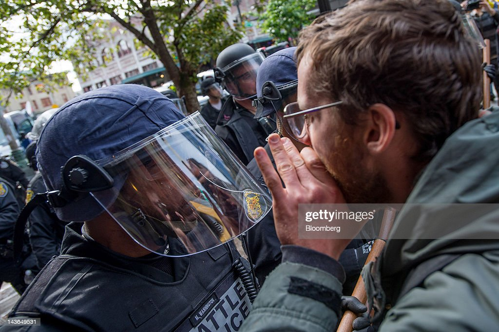 An Occupy Seattle protester, part of an off-shoot of the Occupy Wall Street movement, faces off with a police officer during a May Day rally and anti-capitalist march in Seattle, Washington, U.S., on Tuesday, May 1, 2012. Occupy Wall Street demonstrators took to the streets in May Day protests from New York to California, picketing banks in Oakland with helicopters overhead and sending a singing 'Guitarmy' to Manhattan's Union Square. Photographer: Stuart Isett/Bloomberg via Getty Images