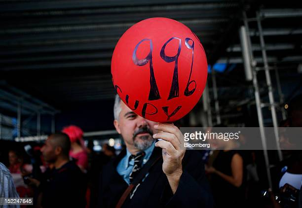 An Occupy Wall Street protester holds a balloon during a demonstration in New York, U.S., on Monday, Sept. 17, 2012. Occupy Wall Street, the protest...