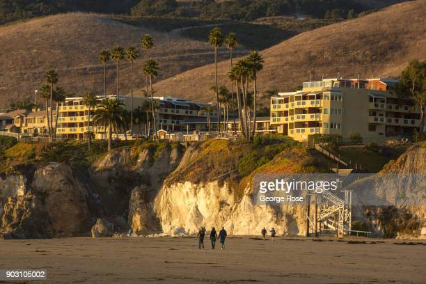 An ocean front hotel is viewed from the beach as the sun sets over the water on December 20 in Pismo Beach, California. With its close proximity to...