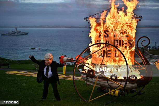 An Ocean Rebellion activist dressed as British Prime Minister Boris Johnson sets fire to a boat during the G7 summit in Cornwall on June 11, 2021 in...