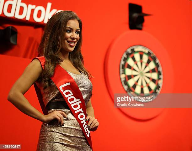 An Oche girl smiles as she poses onstage during the Ladbrokescom World Darts Championship on Day Eight at Alexandra Palace on December 20 2013 in...