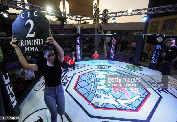 An octagon girl announces the second round of a match during the Iraqi Combat Fighting Championship Mixed Martial Arts Competition in the capital...
