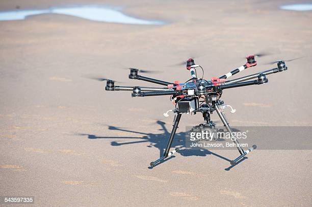 An octocopter drone comes into land on a beach