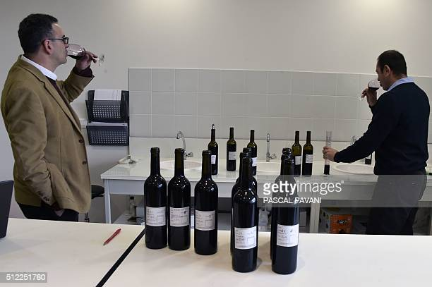 An oenologist and a winemaker taste blended wines from Minervois the Chateau La Mignarde wineyard in his oenological laboratory in...