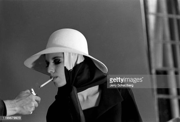 An offcamera person holds a cigarette lighter for an unidentified model dressed in a white hat and a black white scarf Paris France 1962