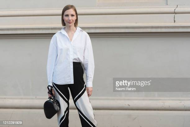 An off-duty model poses in a white shirt and black and white geometric print pants ahead of Runway 1 at Melbourne Fashion Festival on March 11, 2020...