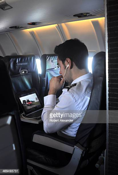 An offduty United Airlines pilot rides as a passenger as he watches a film on his laptop computer as the plane flies between Albuquerque New Mexico...