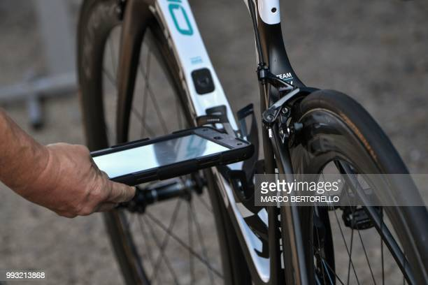 TOPSHOT An offical uses a tablet detecting magnetic flux density as he checks a bicycle for mechanical doping prior to the first stage of the 105th...