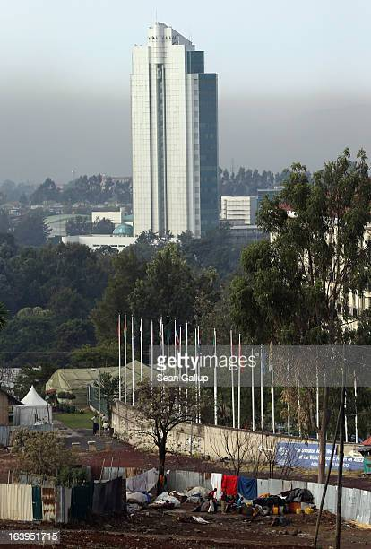 An office building looms over people squatting on vacant land near the city center on March 18 2013 in Addis Ababa Ethiopia Ethiopia with an...