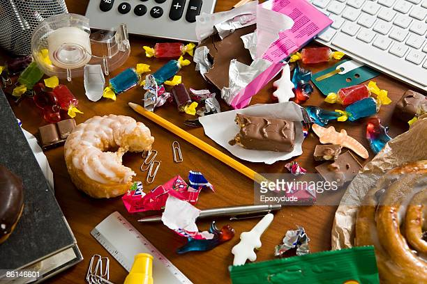 An office desk cluttered with candy and sweets