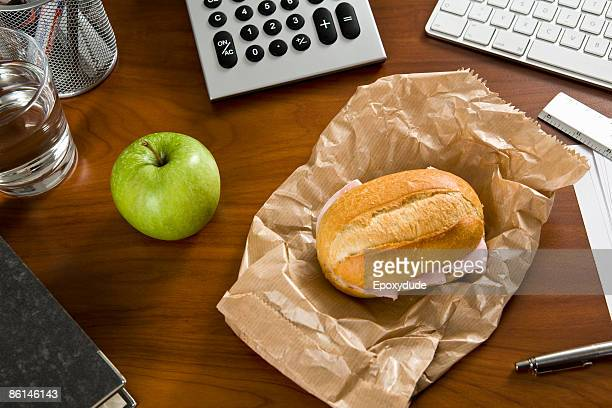 An office desk with office supplies and a sandwich and an apple on it
