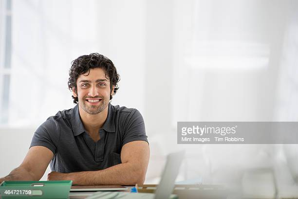 An office in the city. Business. A man sitting in a relaxed pose behind a desk.