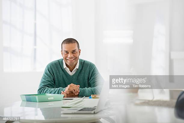 An office in the city. Business. A man sitting with his hands clasped behind a desk.