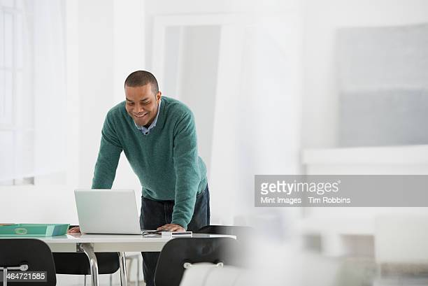 An office in the city. Business. A man standing over a desk, leaning down to use a laptop computer.