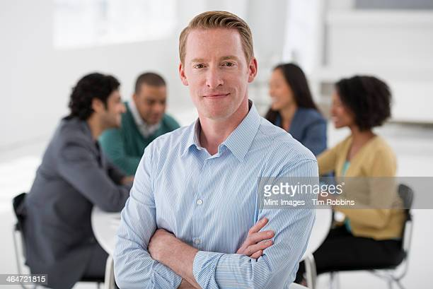 An office in the city. Business. Team meetings. A group sitting down around a table. One person in the foreground. A man smiling confidently.