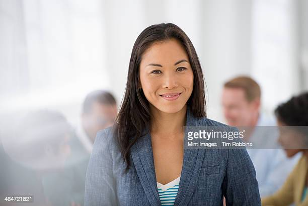 An office in the city. Business. Team meetings. A group sitting down around a table. One person in the foreground. A confident businesswoman. Leader.