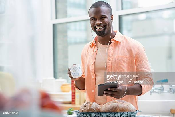 an office or apartment interior in new york city. a man in an orange shirt at the breakfast bar, having a cup of tea.  - オレンジ色のシャツ ストックフォトと画像