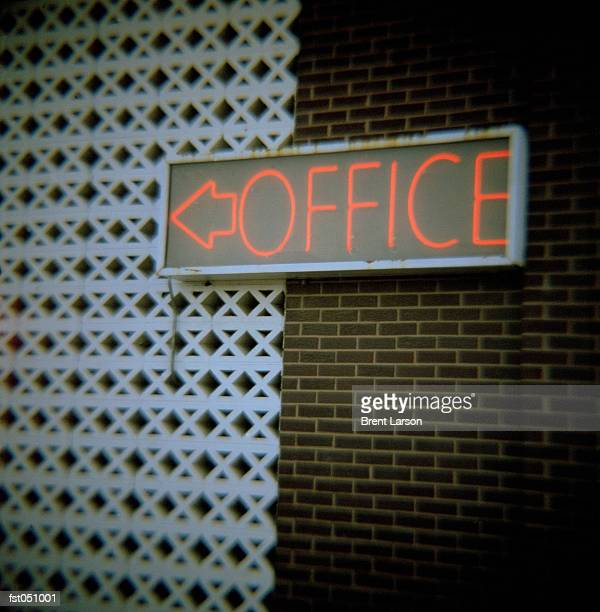 An office sign hanging on a brick wall