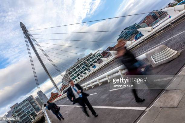 An office worker and other people cross over the River Liffey on the Samuel Beckett Bridge in Dublin Ireland 04 June 2015