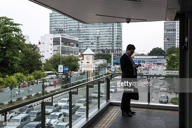 An office worker checks his mobile phone while standing on a walkway in Kuala Lumpur, Malaysia, on Tuesday, March 18, 2014. Malaysia, aspiring to...
